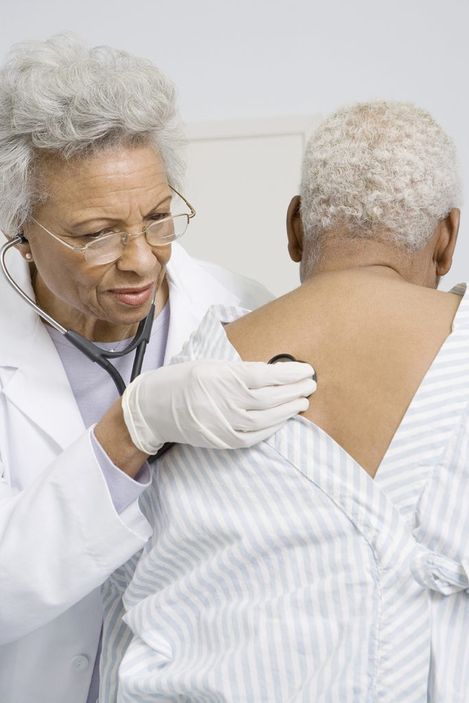 Senior female doctor checking patient's heart and lungs using stethoscope in clinic.
