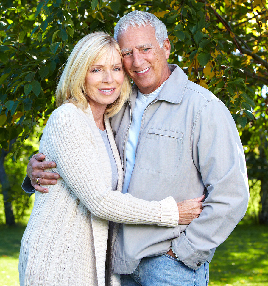 Smiling senior couple hugging under trees on a sunny day.