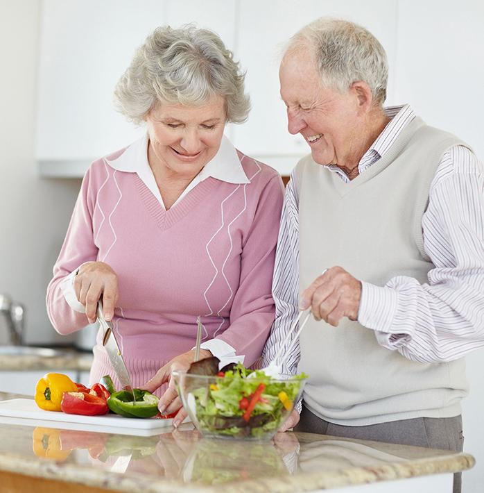 Senior couple preparing salad together.