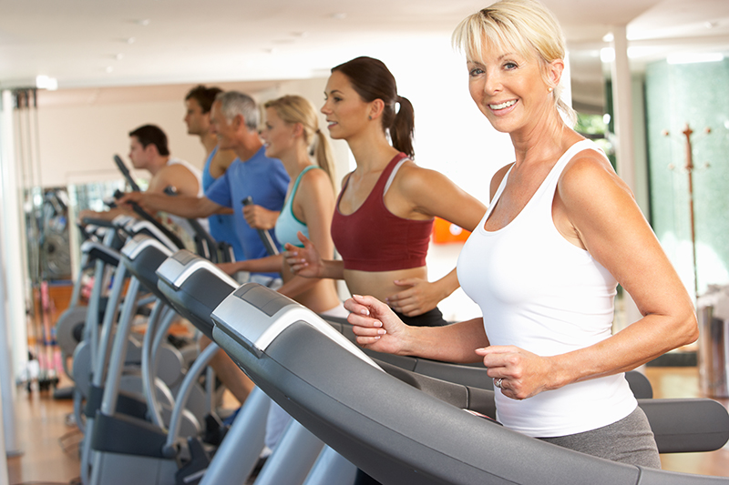 Senior woman smiles while working out on a treadmill. Keep up your physical activity as you age.