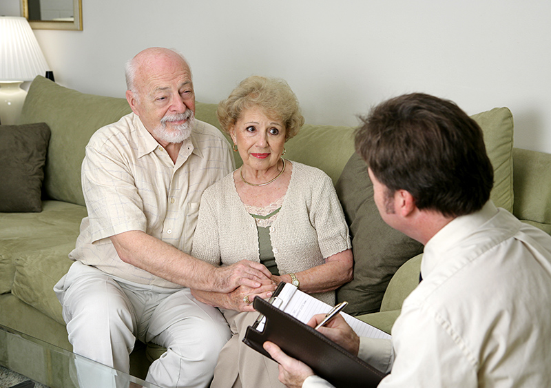 A senior couple talking with a social worker in their home.