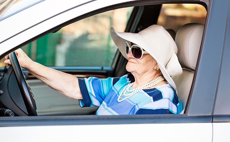 Senior woman in sunglasses driving a car.