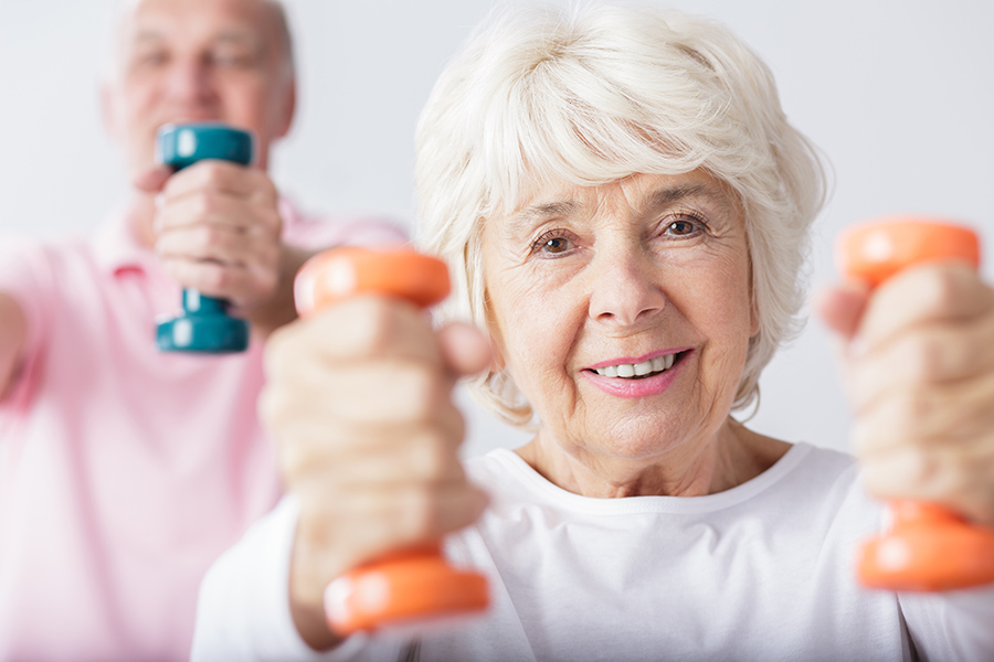Smiling senior woman lifting two dumbbells.