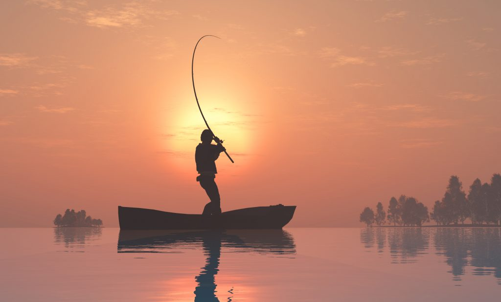 Silhouette of a fisherman in a boat. with a yellow sun and orange sky in background.