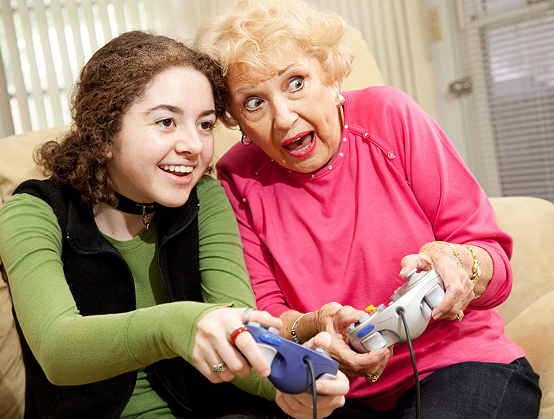 Grandmother and granddaughter playing an exciting video game together with smiles and laughter.